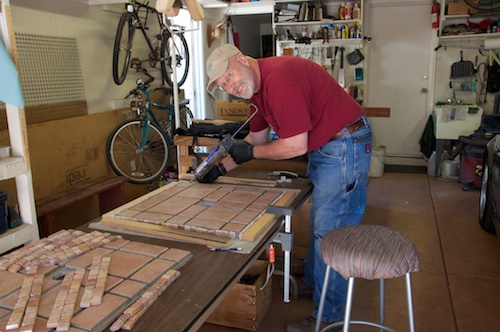 Rich doing the tile work for the new rolling patio umbrella stands.